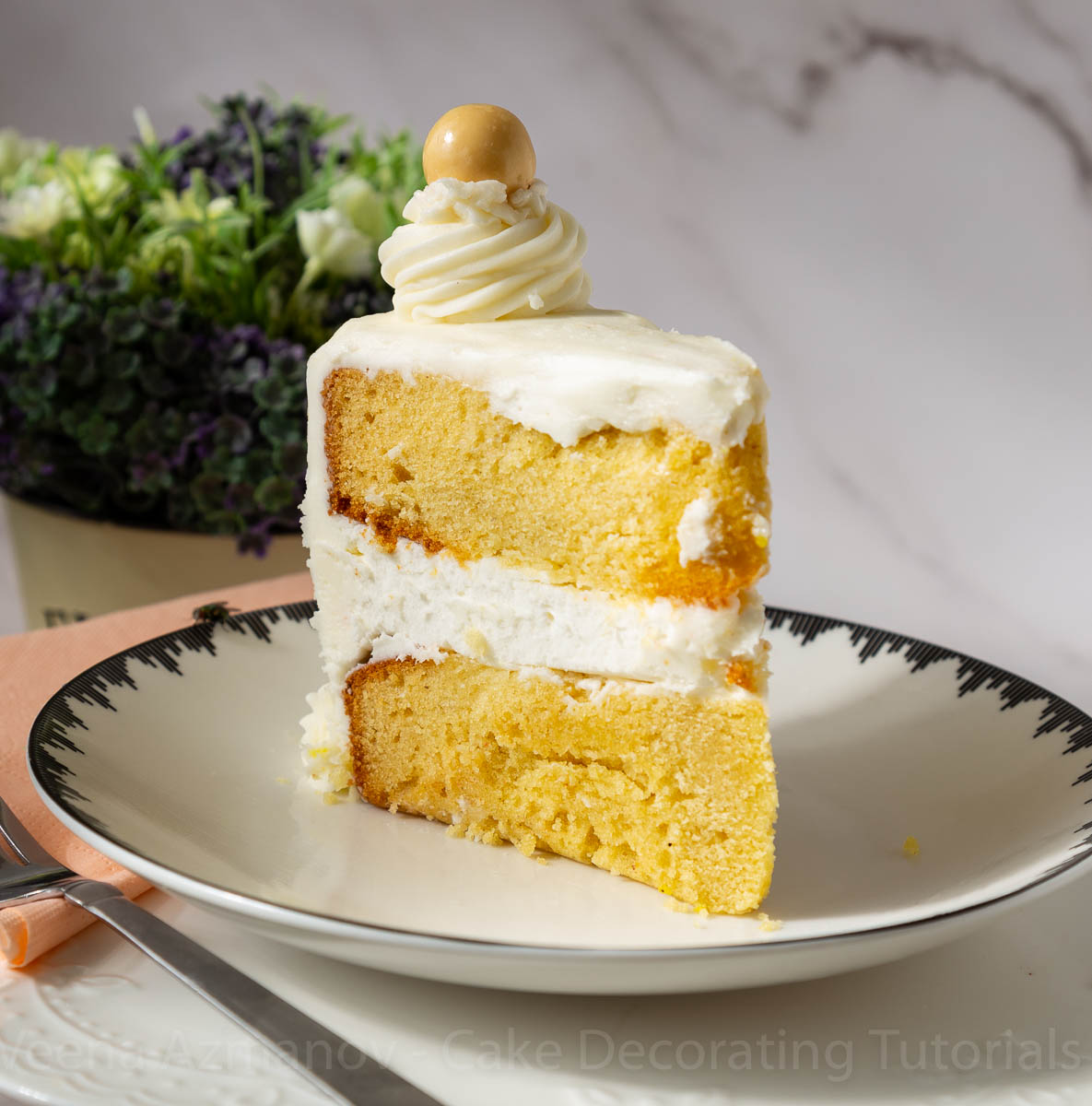 A slice of frosted cake on a plate with vanilla frosting.