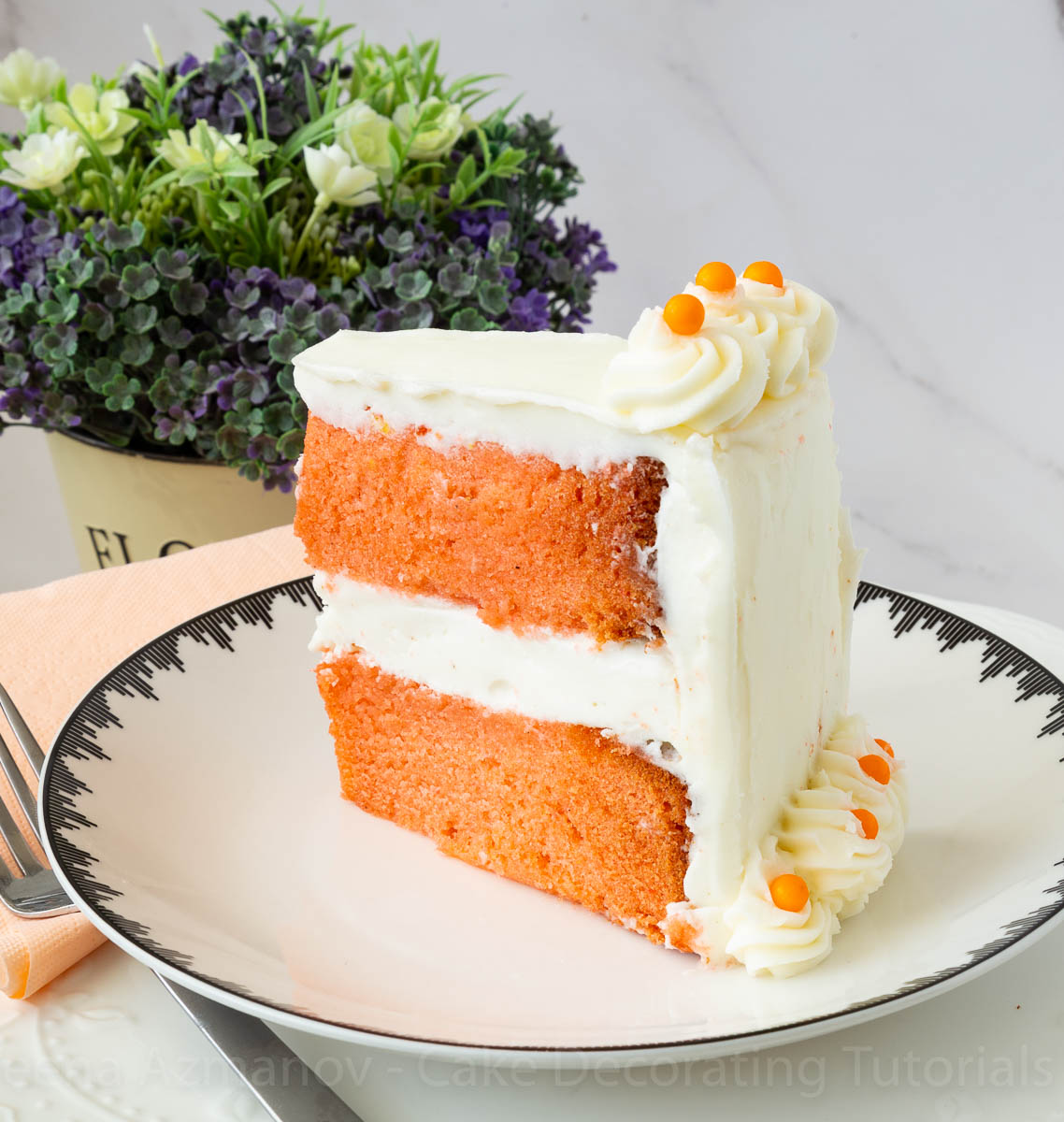 A slice of orange layer cake on a plate.