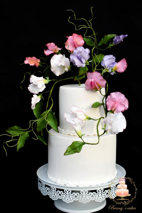 A beautiful wedding cake topped with colorful sugar work