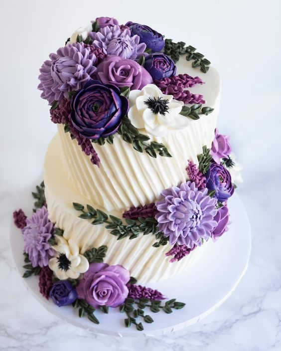 purple and white buttercream flowers topped on a 2 tier cake
