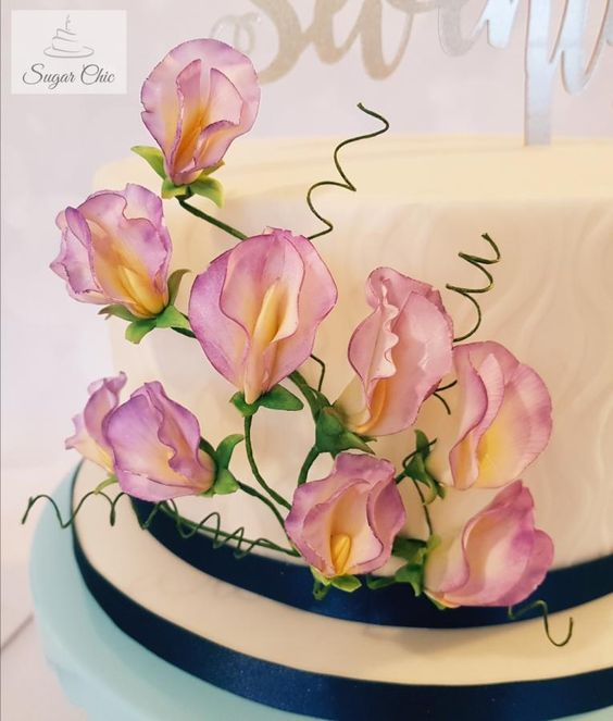 Fondant cake topped with purple sugar sweet pea flowers