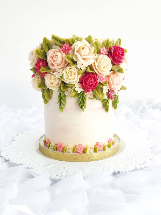 roses and leaves piped on a white cake
