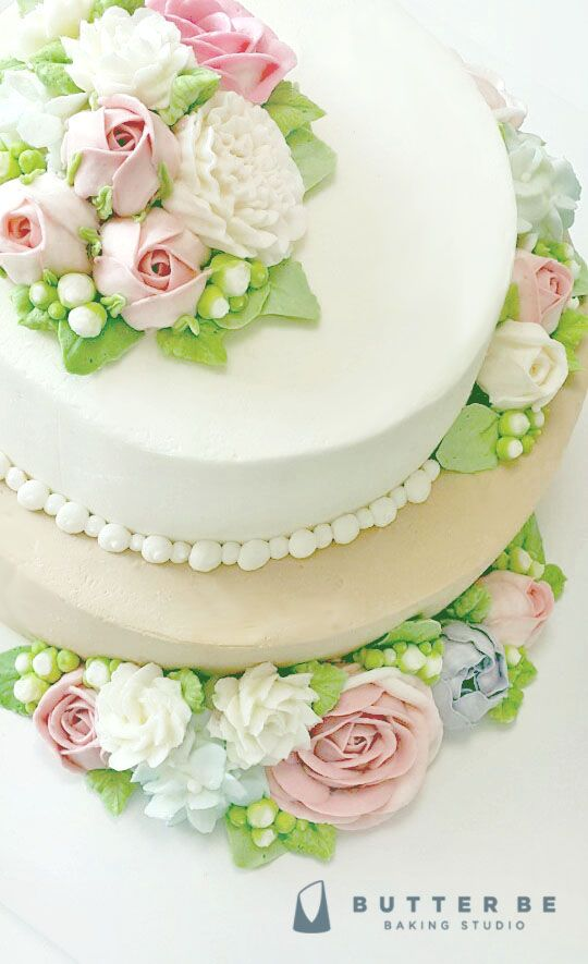 White buttercream cake with buttercream pink flowers and leaves