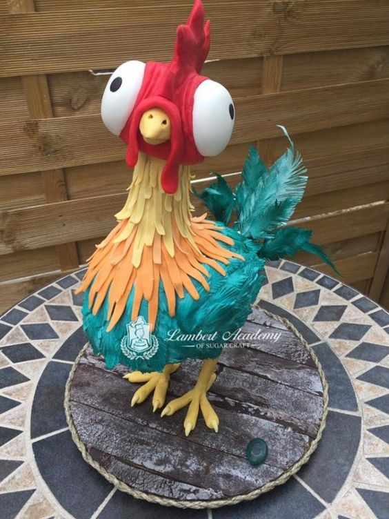 A 3d cock cake with colorful fur made of fondant