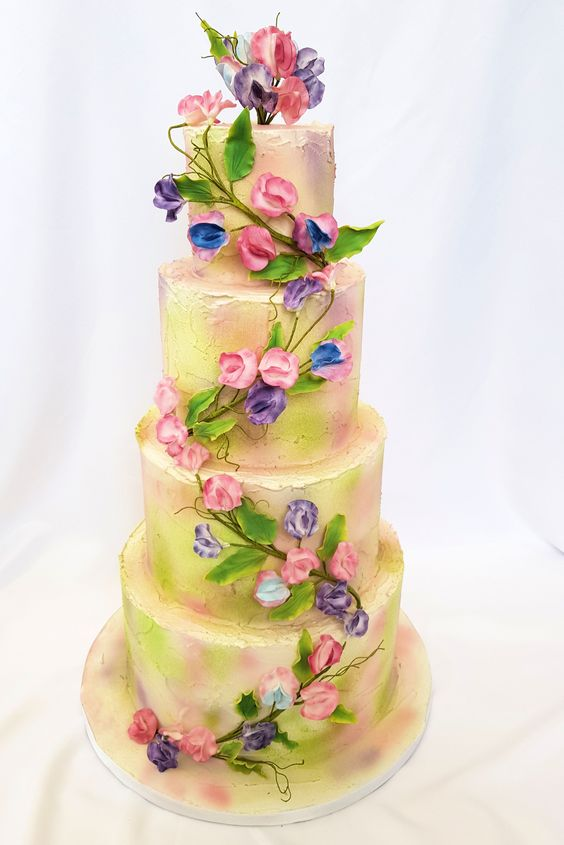 A yellow tier cake topped with sugar sweet pea flowers in pink, blue, purple