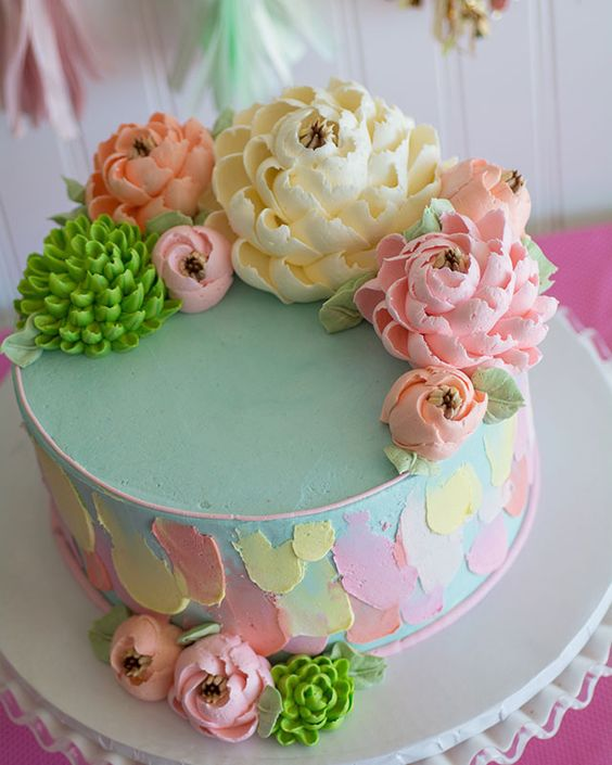 Pastel color buttercream flowers topped on a buttercream cake