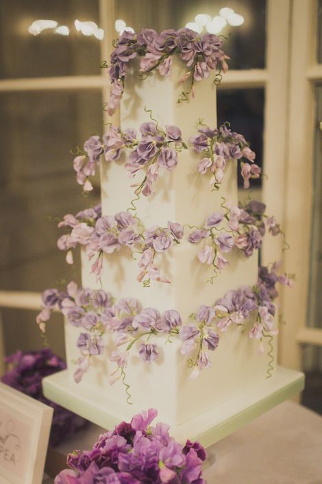 A gorgeous square tier wedding cake with a gumpaste purple sweet pea flowers