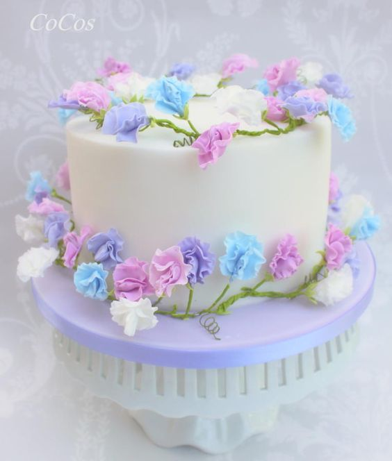 A simple cake topped with sugar flowers in light pink, light purple and blue