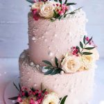 A beautiful fresh flower cake with white beads