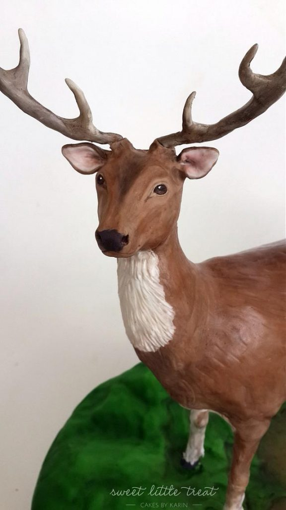 A full size deer cake made with fondant with sugar work