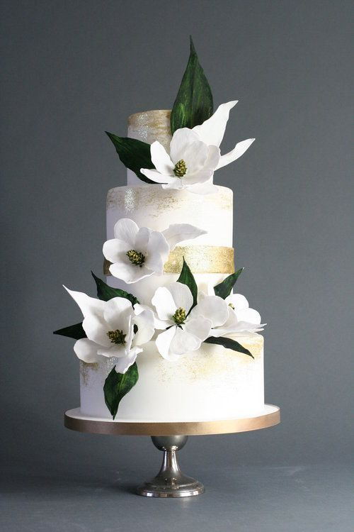 A 3 tier wedding cake with white sugar flowers
