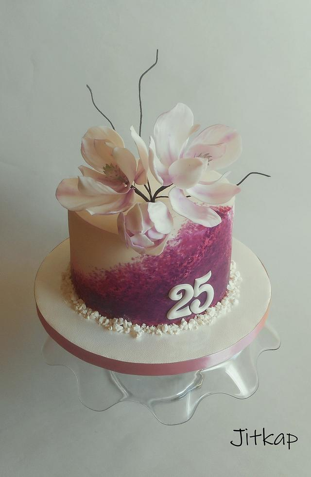 Purple cake topped with a huge magnolia with purple shades