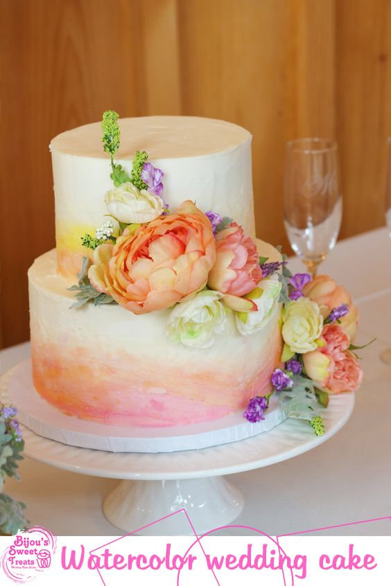 An elegant cake brushed with shades of orange and topped with flowers