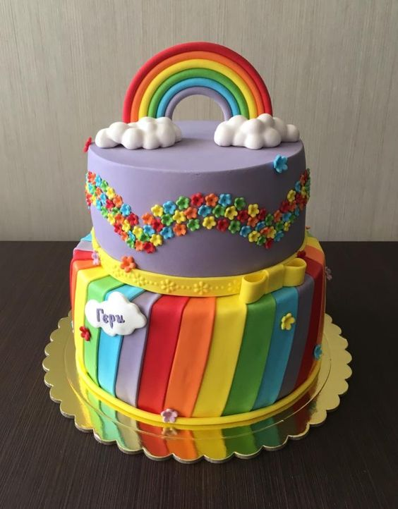 A 2 tier rainbow theme cake with clouds and colors