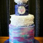 a 3 tier cake painted with edible colors of blue and pink