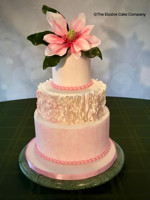 Pink Magnolia flower on a wedding cake with ruffles