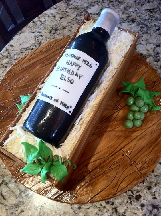 A wine bottle cake made with a cake crate and green fondant grapes