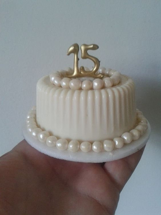 a small cake with pearls and white fondant