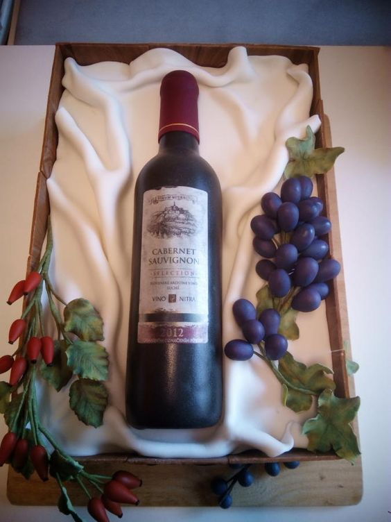 A wine bottle crate cake with edible fondant grapes and leaves