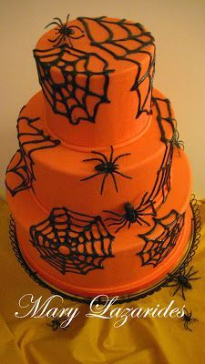 2 tier orange cake with spider webs iced on it with a sugar spiders