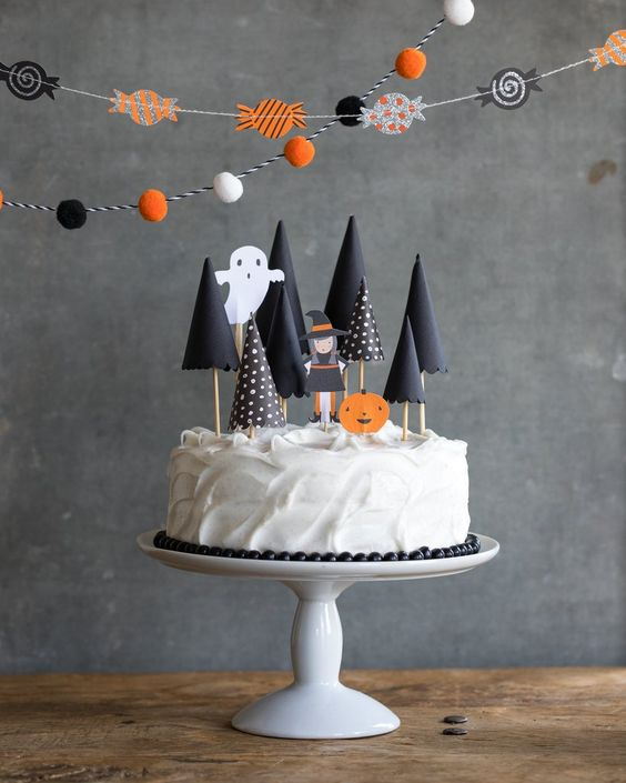 a simple white frosted cake with cone shaped trees made from black paper