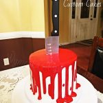 white cake with red icing dripping to make it look like blood and a steel knife poked inside for a halloween cake theme party