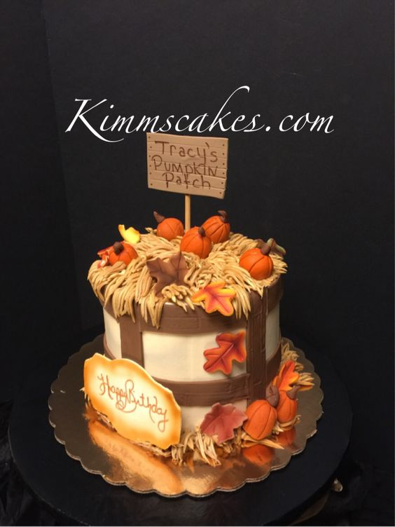 Cake topped with sugar fondant orange pumpkins and brown leaves