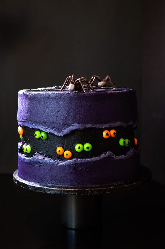 a gothic theme cake with spiders on it, cake is royal blue in color