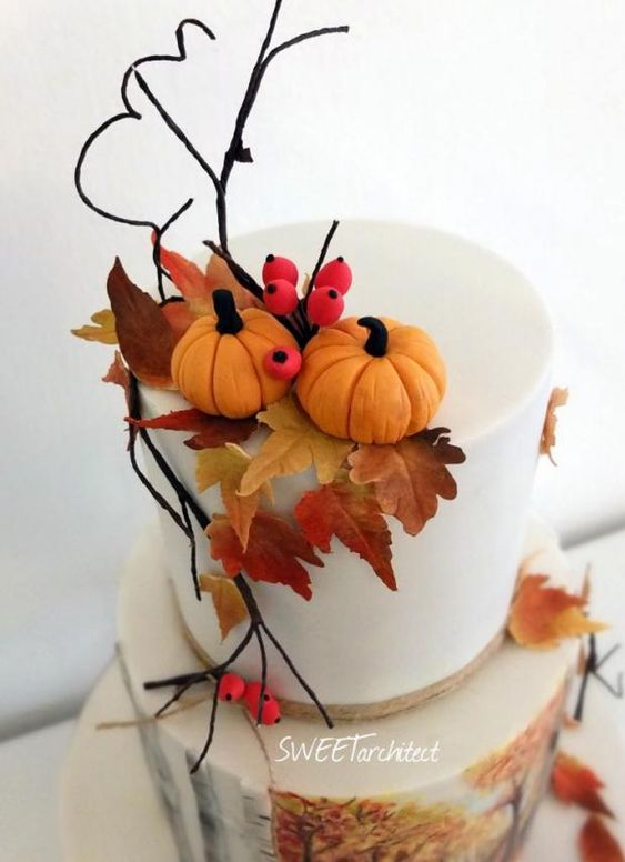 A two tier white fondant cake with sugar brownish orange leaves and pumpkins
