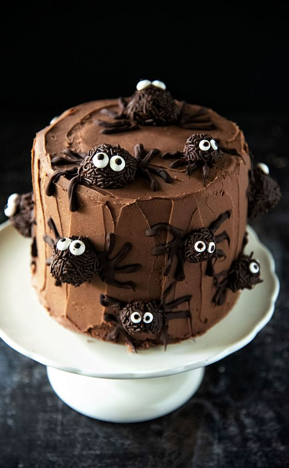 a chocolate cake with spiders made of chocolate all around the cake on a white turn table