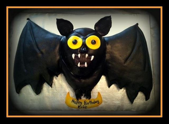 A simple black bat theme cake for halloween with yellow eyes and big black wings