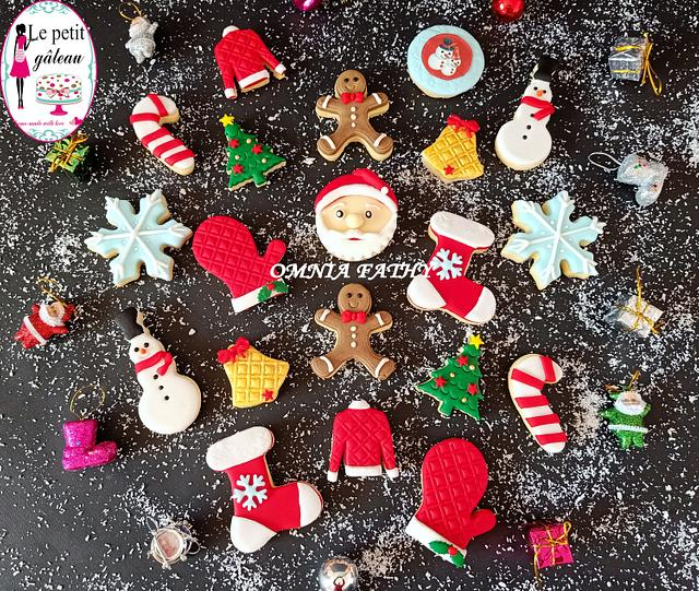 a black background with snowflakes sprinkled and fancy christmas cookies spread around