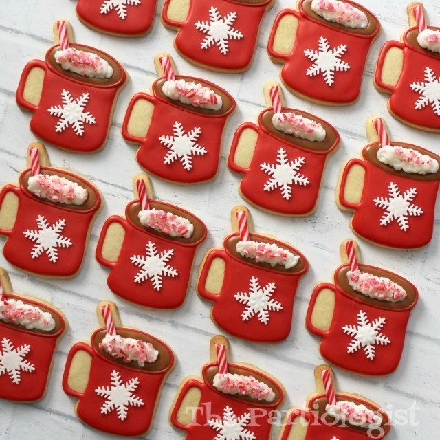hot chocolate and marshmallow theme red cookies iced with royal icing and fondant cut snowflakes