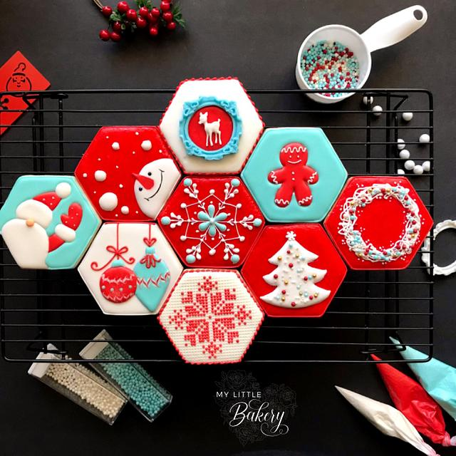 A black background with hexagon shaped red, blue and white christmas decorated cookies