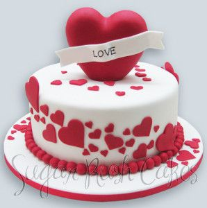 A fondant heart with love written on it inserted in the center of the cake
