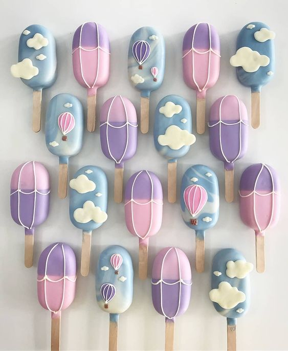 purple and blue cake on a stick with fondant clouds on it
