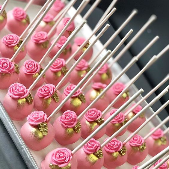 a pink cake pop with colorful flowers of fondant and gold painted leaves