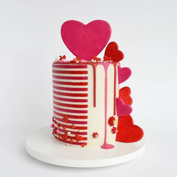 Red and white stripe cake with red and pink hearts pushed all around the tall cake - Valentine's Day Cake Tutorials