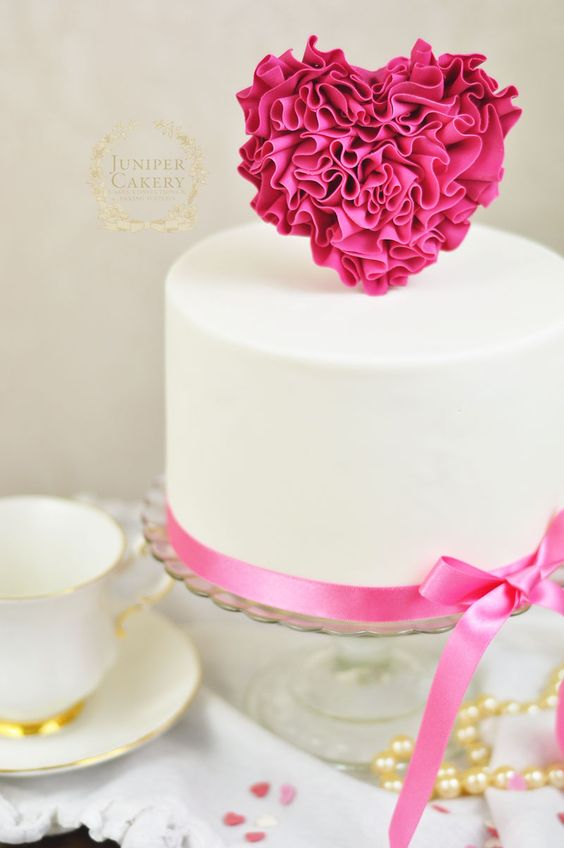 A standing pink heart on an cake made with pink ruffles and put on a white fondant cake