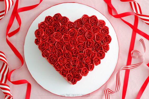red roses all over a heart cake