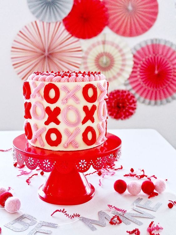 X & 0 written with cream frosting all around the cake in red and pink