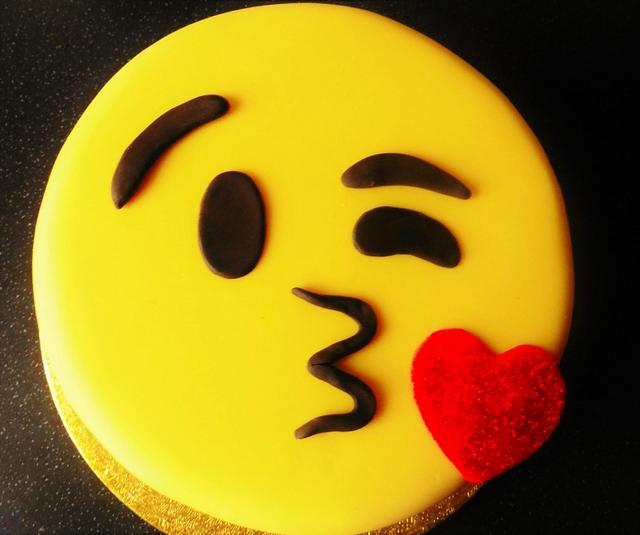 a simple yellow round cake made to look like a kissing emoji