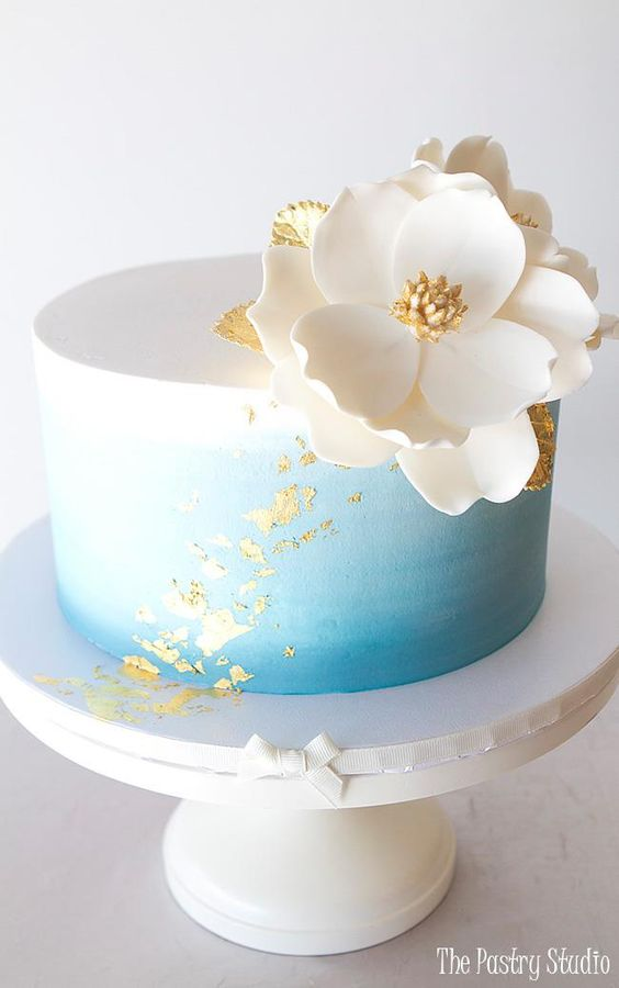 A blue and white cake decorated with a chocolate flower white in color - Chocolate Flower Tutorials
