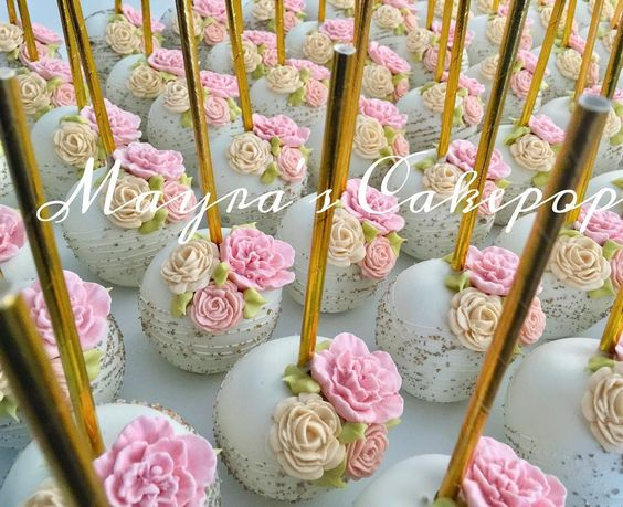 pastel color cake on a golden stick with fondant flower work
