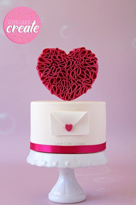 A red fondant ruffle heart shape pushed into the cake with a toothpick to make it stand - Valentine's Day Cake Tutorials