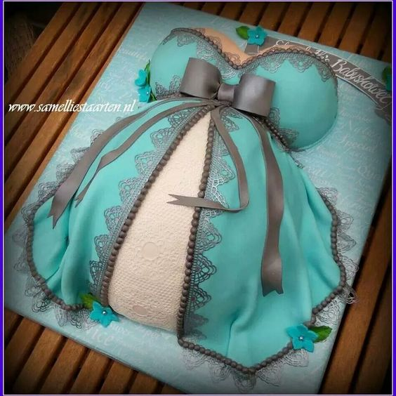 a pregnant lady theme cake with a fondant baby bump in a fondant green dress with black lace