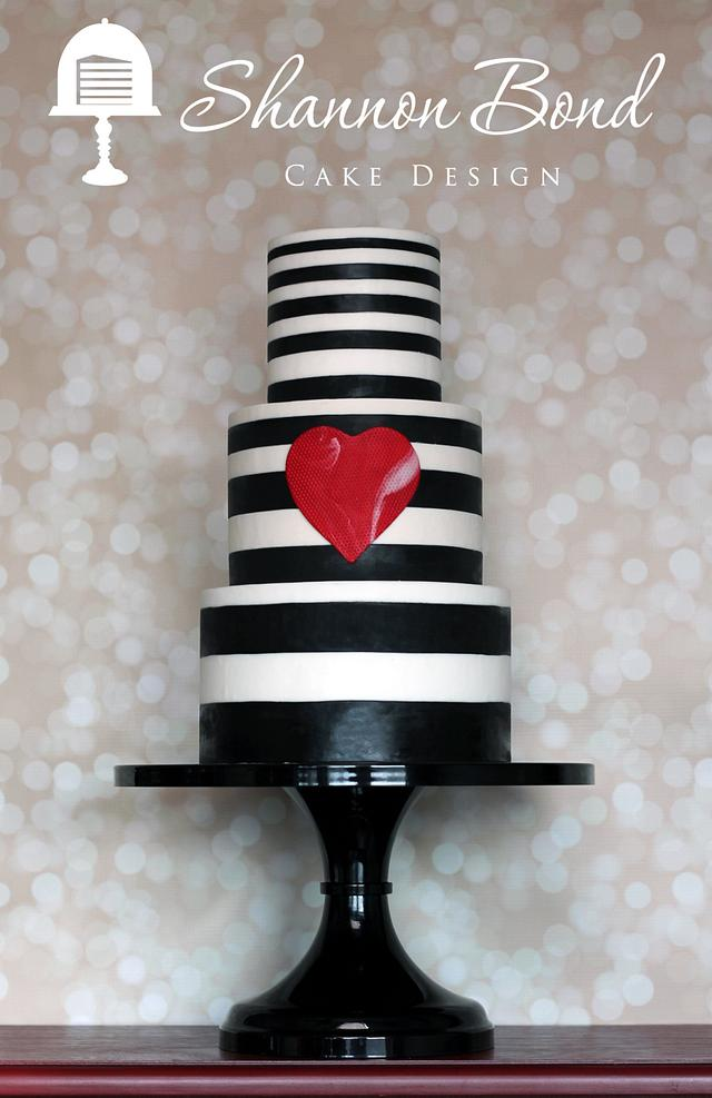 A 3 tier white fondant cake with black strips on it from top to bottom and then a red heat stuck on the center tier - Valentine's Day Cake Tutorials