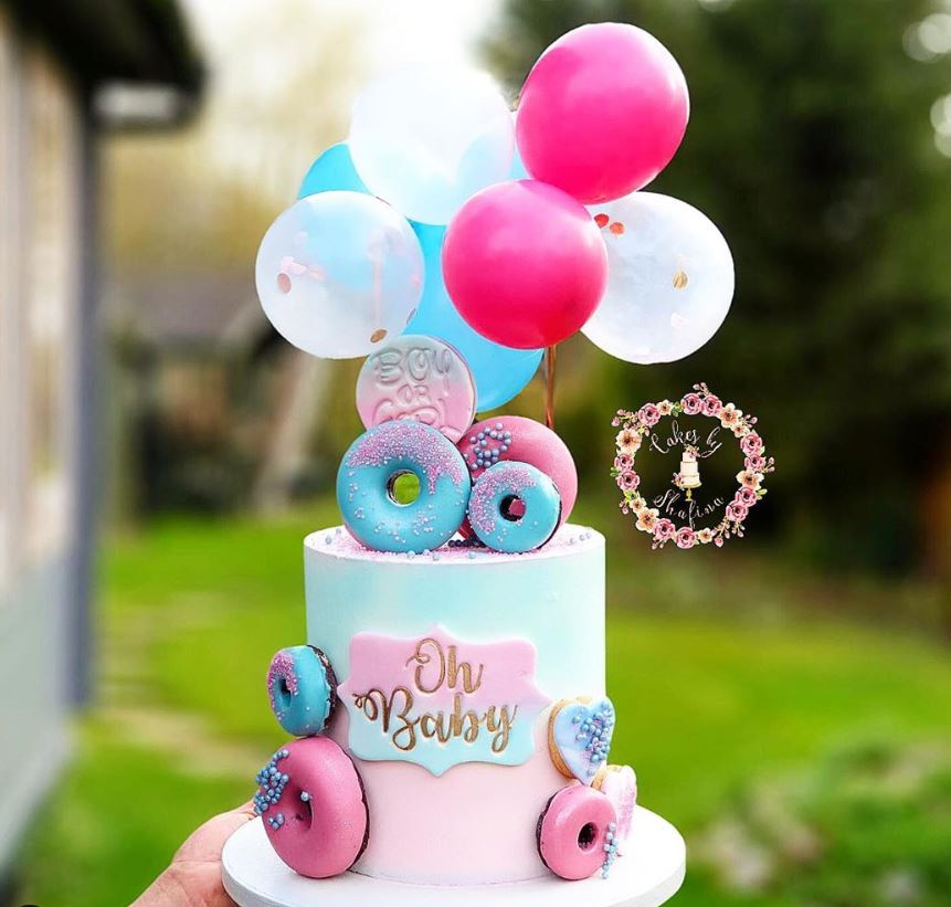 Oh baby written on the cake with a blue and pink combination and colorful donuts around the cake - Baby shower cake Tutorials