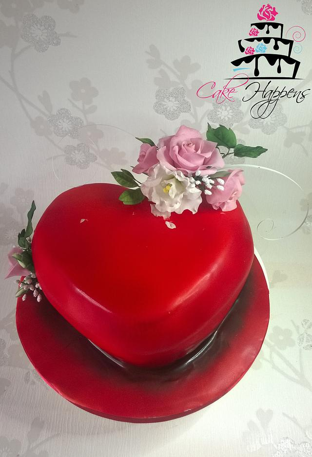 red heart shaped cake with a sugar flower spray on it of pink and white flowers with green leaves