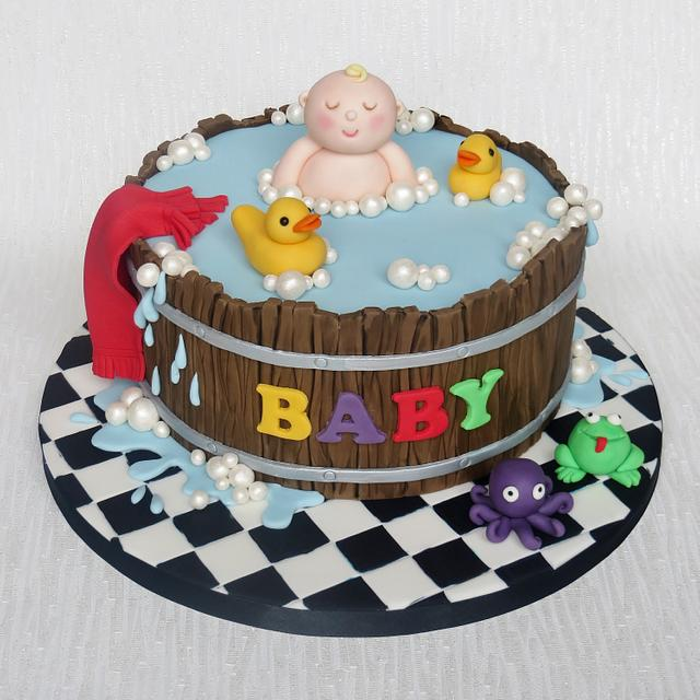 a wooden drum shaped cake with water effect and ducks swimming in it with a fondant baby